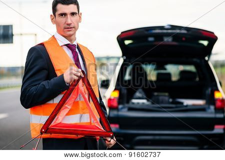 Man with car breakdown erecting warning triangle on road