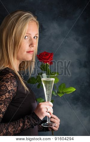 a young woman in evening dress with a red rose and a glass of sparkling wine or champagne. symbolic photo for valentine's day, romance and wedding