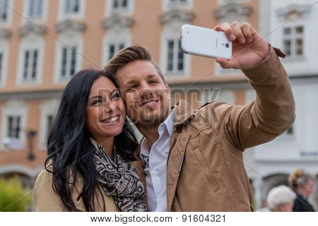 a young couple making a self portrait with a mobile phone. selfies are in.