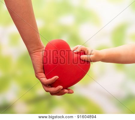Man and child hands holding heart