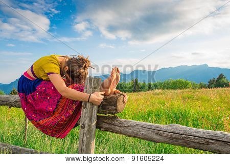 Casual Girl Relaxes Doing Stretching And Yoga Alone In The Mountains Over A Fence In A Beautiful Spr