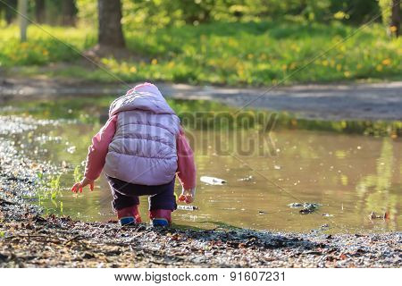 Toddler girl looking for pebbles on big summer puddle bank