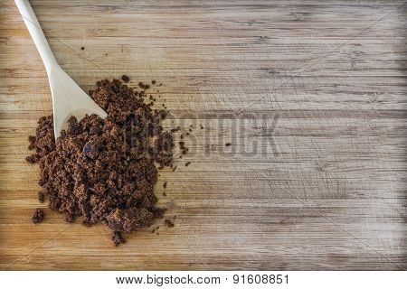 Dark muscovado sugar in a wooden spoon