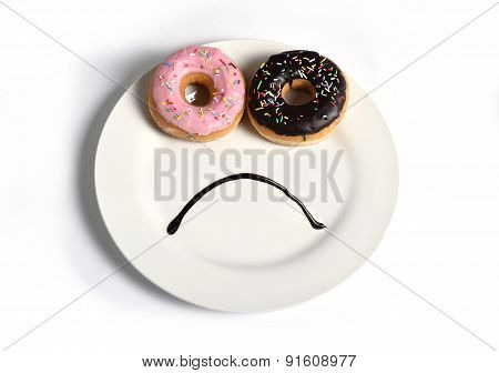 Sad Face Made On Dish With Donuts As Eyes And Chocolate Syrup Mouth In Sugar Sweet Addiction