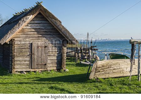 Rustic Fisherman Utility House And Boats At Sea Coast, Modern City On Background