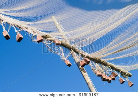 Closeup On Old Style Fishing Net Hanging To Dry Under Sun