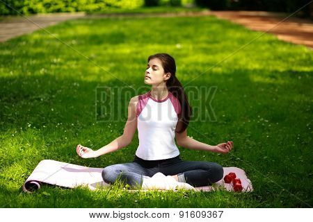 Sportive Young Woman Relaxing In Sunshine, Doing Yoga Exercises, In Green Park