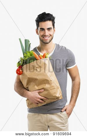 Handsome young man carrying a bag full of vegetables, isolated over gray background