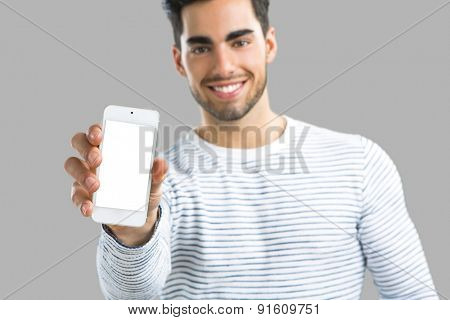 Handsome young man showing something on his phone, isolated over gray background