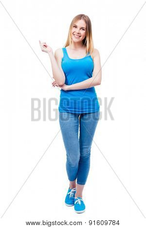 Full length portrait of a cheerful beautiful woman isolated on a white background. Wearing in blue shirt and jeans. Looking at camera