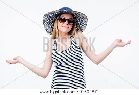 Happy woman in hat and sunglasses shrugging her shoulders over gray background