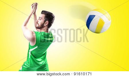 Volleyball player on green uniform on yellow background