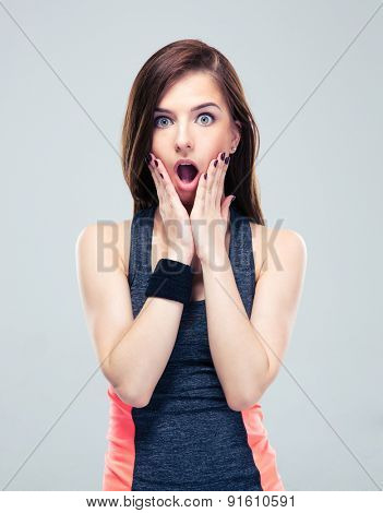 Shocked fitness woman in sportswear standing on gray background. Looking at camera