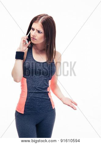 Fitness woman in sports wear talking on the phone isolated on a white background. Looking away