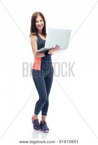 Happy fitness woman using laptop isolated on a white background and looking at camera