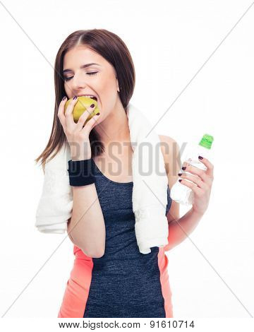 Fitness woman eating apple and holding bottle with water isolated on a white background