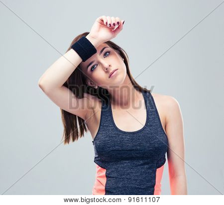 Beautiful fitness woman wipes the sweat from his brow on gray background and looking at camera
