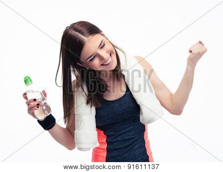 Happy fitness woman with towe and bottle of water celebrating her victory isolated on a white background. Looking at camera
