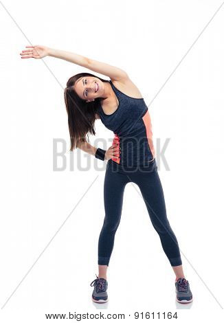 Full length portrait of a happy sporty woman doing stretching exercise isolated on a white background. Looking at camera