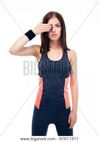 Fitness beautiful woman covering her eye with hand and looking at camera. Isolated on a white background