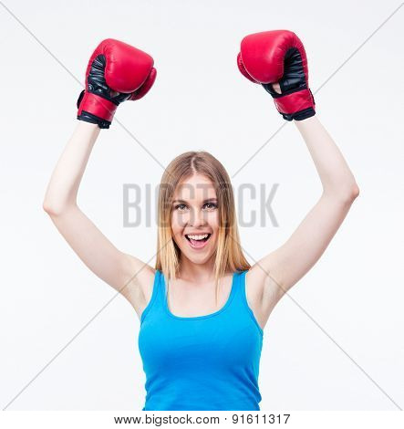 Cheerful woman in boxing gloves celebrating victory isolated on a whtie backgorund. Looking at camera