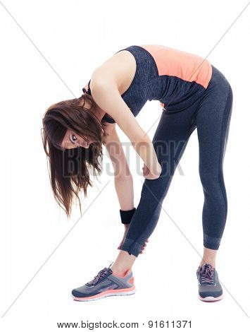 Full length portrait of a young fitness woman doing stretching exercise isolated on a white background