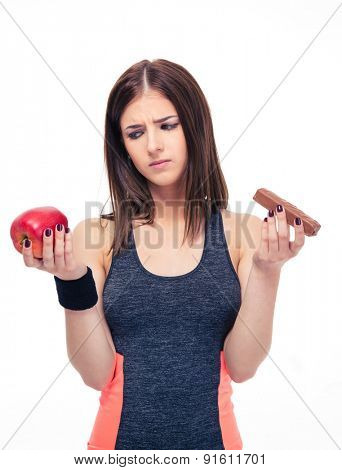 Sports woman making choice between healthy apple and unhealthy chocolate isolated on a white background.