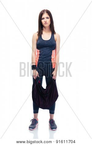 Full length portrait of a tired cute woman standing with sports bag isolated on a white background. Looking at camera