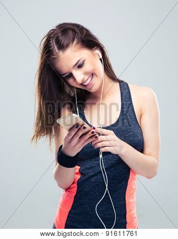 Happy sports woman in headphones using smartphone over gray background