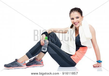 Happy woman sitting on the floor with bottle of water and towel isolated on a white background. Looking at camera