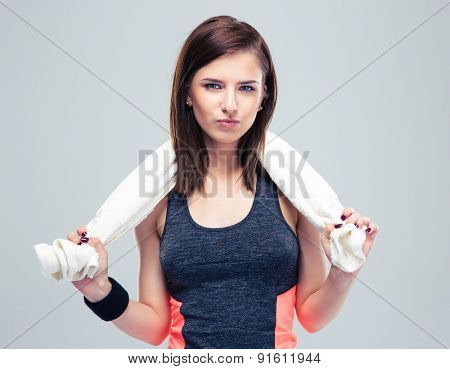 Pretty fitness woman with towel on gray background. Looking at camera