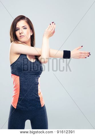 Young fitness woman stretching hands on gray background and looking at camera