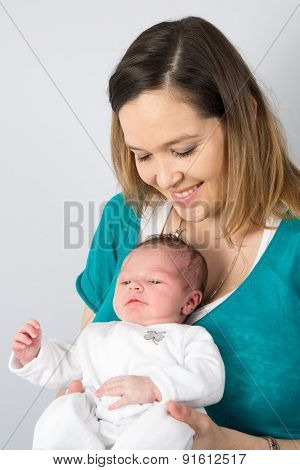 Mother Holding Her New Born Baby , Smiing At The Camera