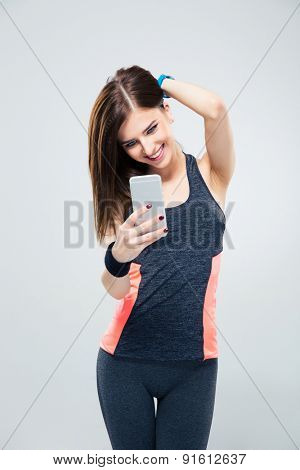 Sportive woman using smartphone over gray background