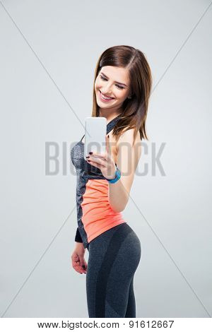 Happy woman making photo on smartphone over gray background