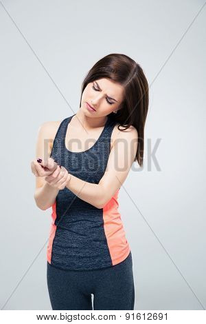 Fitness young woman with wrist pain over gray background
