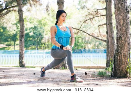 Fitness woman doing stretching exercise outdoors in park