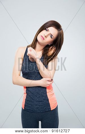Sports woman having pain in elbow over gray background. Looking at camera