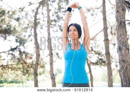 Sporty woman in headphones stretching hands outdoors in park. Looking away