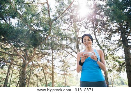 Smiling sporty woman using smartphone outdoors with trees on background