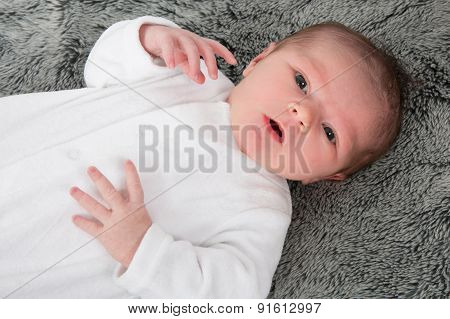 Happy New Born Baby Laying In Grey Blanket Looking At The Camera