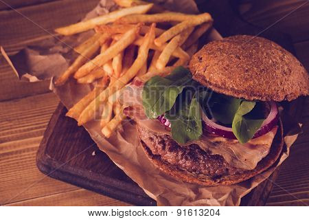 Burger And French Fries Close Up On Vintage Style.