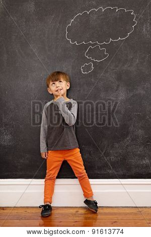Little Boy Thinking With A Thought Bubble On The Blackboard
