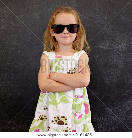 Cute Little Girl In Shades Against A Black Wall