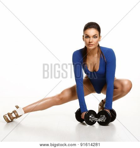 Woman Bodybuilder In Blue Bodysuit, Performs An Exercise With Dumbbells. Studio Shot.