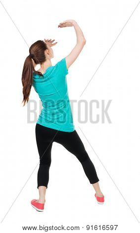 back view. woman in sportswear hands from what is falling from above. Isolated over white background. Sportswoman hands protected from the falling from the top of the object.