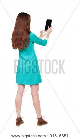 back view of standing young beautiful  girl with tablet computer in hands of.  backside view of person.  Isolated over white background. girl in blue dress with brown shoes photographed using  tablet.