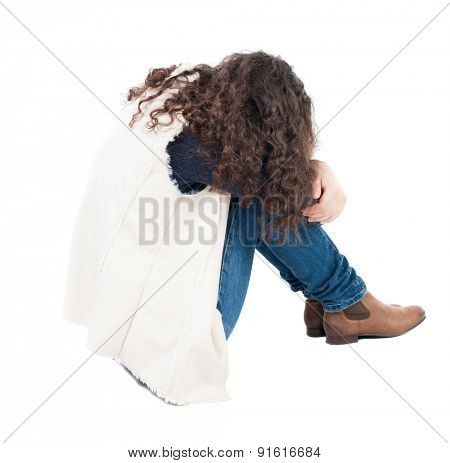 back view curly girl sitting and crying. girl relaxes. Rear view people collection. backside view of person.   A girl in a white tank top sitting on the floor with his head resting on his legs.
