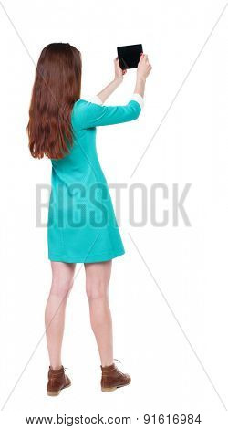 back view of standing young beautiful  girl with tablet computer in the hands of.   Isolated over white background. The girl in a blue dress with brown shoes photographed myself tablet