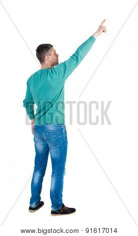Back view of  pointing young men in jeans. Young guy  gesture. Rear view people collection.    Isolated over white background. The guy in the green jacket stands sideways and shows a finger at right